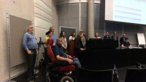 Die Mitglieder des Ausschusses stehen vorne auf der Bühne und stellen sich vor.