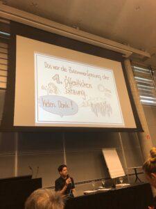 Michael Hanl spricht zum Publikum. Er unterstützt die Veranstaltung mit bildnerischen Zusammenfassungen und einfacher Sprache. Hinter ihm sieht man seine Präsentation. Darauf steht: Das war die erste öffentliche Sitzung des Salzburger Monitoringausschusses.