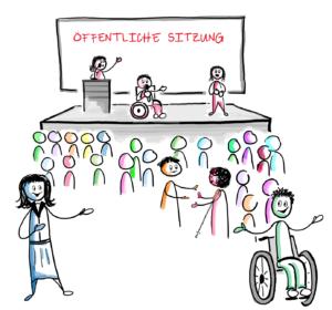 Man sieht drei Personen auf der Bühne stehen. Eine Person steht hinter einem Pult. Eine Person sitzt im Rollstuhl. Eine Person steht und spricht in Gebärdensprache. Dahinter sieht man eine Tafel. Darauf steht: Öffentliche Sitzung. Viele Teilnehmerinnen und Teilnehmer stehen vor der Bühne.
